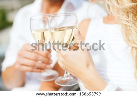 summer holidays and dating concept - couple drinking wine in cafe in the city - stock photo