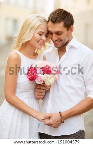 summer holidays and dating concept - couple with bouquet of flowers in the city - stock photo