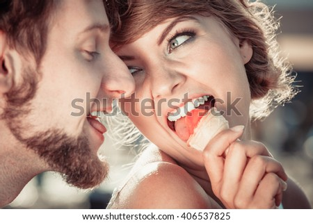 Summer holidays and happiness concept. Young couple eating ice cream outdoor in the city - stock photo