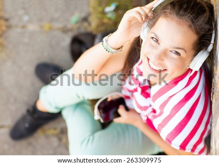 summer holidays and technology concept - teenage girl with headphones listening to music outside - stock photo