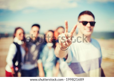summer holidays and teenage concept - close up of male hand showing v-sign with fingers with friends on the back - stock photo