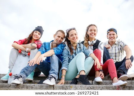 summer holidays and teenage concept - group of smiling teenagers hanging outside - stock photo