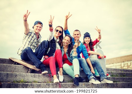 summer holidays and teenage concept - group of smiling teenagers hanging outside and showing v-sing