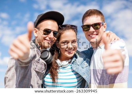 summer holidays and teenage concept - group of smiling teenagers showing thumbs up - stock photo