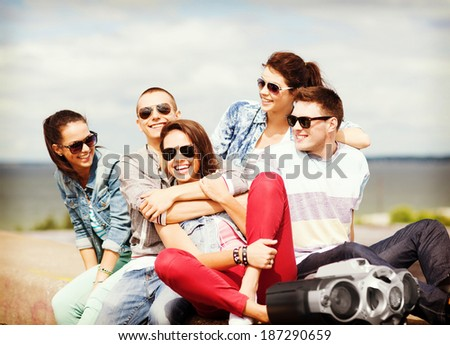 summer holidays and teenage concept - group of teenagers hanging out - stock photo