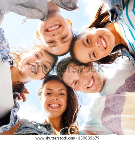 summer holidays and teenage concept - group of teenagers looking down - stock photo