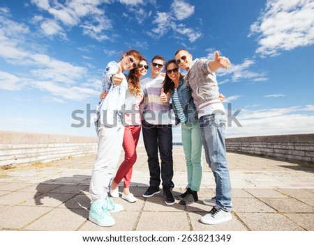 summer holidays and teenage concept - group of teenagers showing thumbs up - stock photo