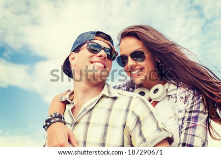 summer holidays and teenage concept - smiling teenagers in sunglasses having fun outside - stock photo
