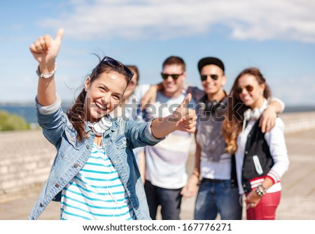 summer holidays and teenage concept - teenage girl in sunglasses and headphones hanging out with friends outside and showing thumbs up - stock photo