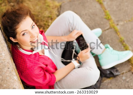 summer holidays and teenage concept - teenage girl with headphones listening to music outside - stock photo