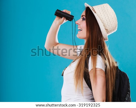 Summer holidays and tourism concept. Lovely tourist woman with backpack looking through binoculars on blue sideview - stock photo