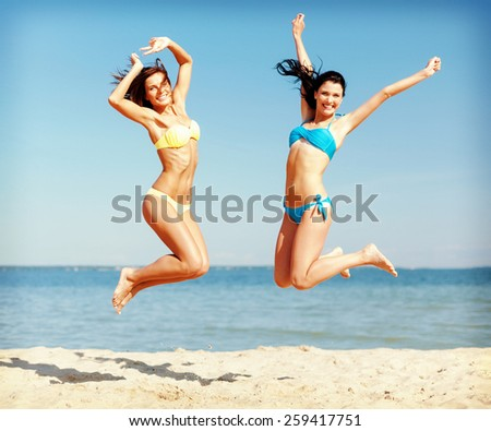 summer holidays and vacation concept - beautiful girls in bikini jumping on the beach - stock photo