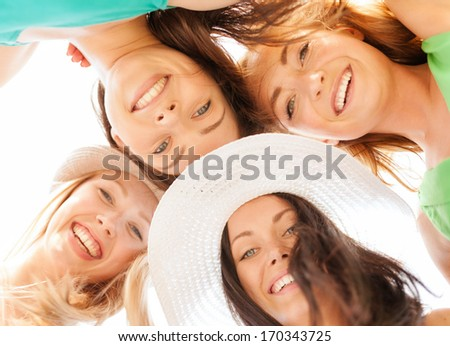 summer holidays and vacation concept - faces of girls looking down and smiling - stock photo