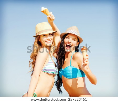 summer holidays and vacation concept - girls in bikini with ice cream on the beach - stock photo