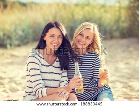 summer holidays and vacation concept - girls with drinks on the beach - stock photo