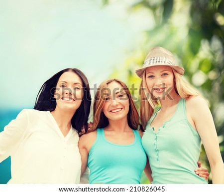 summer holidays and vacation concept - group of smiling girls chilling on the beach - stock photo