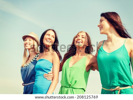 summer holidays and vacation concept - smiling girls walking on the beach - stock photo