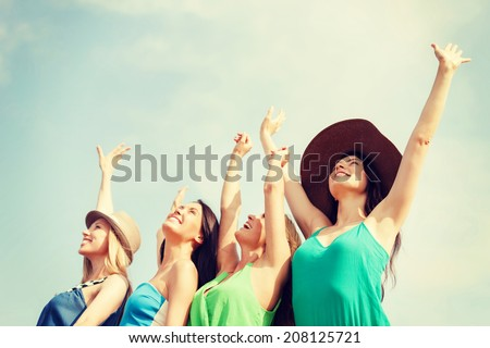 summer holidays and vacation concept - smiling girls with hands up on the beach - stock photo