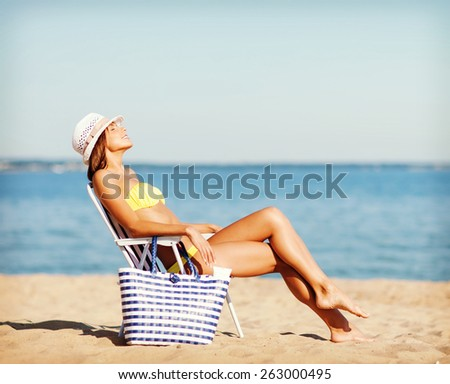 summer holidays and vacation - girl in bikini sunbathing on the beach chair - stock photo