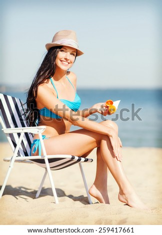 summer holidays and vacation - girl putting sun protection cream on the beach chair - stock photo