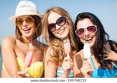 summer holidays and vacation - girls in bikinis eating ice cream on the beach