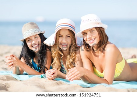 summer holidays and vacation - girls in bikinis sunbathing on the beach - stock photo