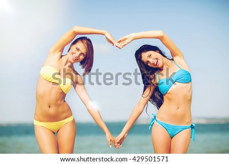 summer holidays and vacation - girls making heart shape with hands on the beach - stock photo