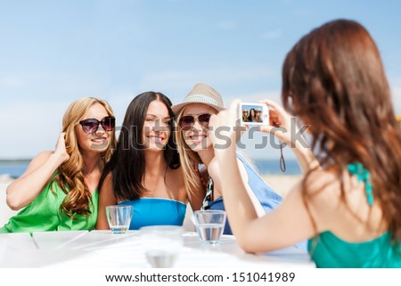 summer holidays and vacation - girls taking photo with digital camera in cafe on the beach - stock photo
