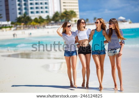 summer holidays and vacation - girls walking on the beach laughing. summer holidays and vacation - group of girls chilling on the beach near the ocean. girls having fun on the beach - stock photo
