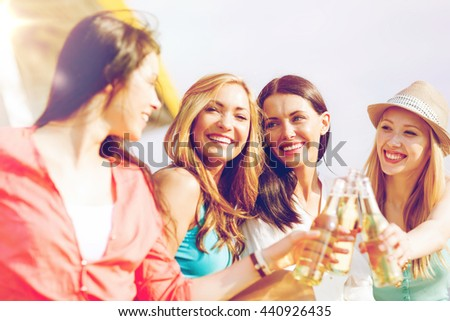 summer holidays and vacation - girls with drinks on the beach