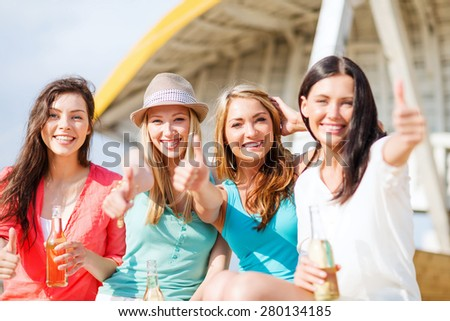 summer holidays and vacation - girls with drinks showing thumbs up on the beach