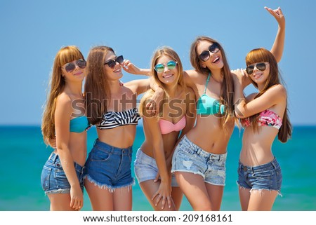 summer holidays and vacation - group of girls chilling on the beach
