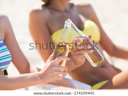 summer holidays and vacation - two girls in bikinis with drinks on the beach chairs - stock photo