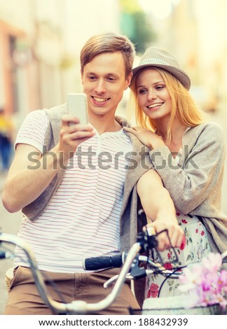summer holidays, apps and dating concept - couple with bicycles and smartphone in the city - stock photo