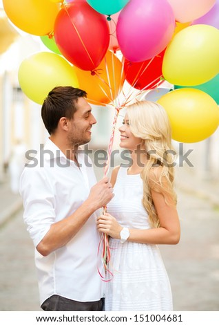summer holidays, celebration and dating concept - couple with colorful balloons in the city - stock photo