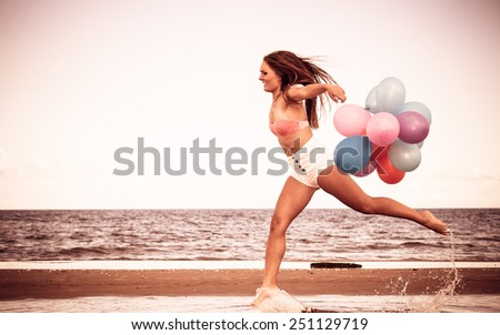 Summer holidays, celebration and lifestyle concept - attractive athletic woman teen girl jumping with colorful balloons outside on beach, aged retro tone - stock photo