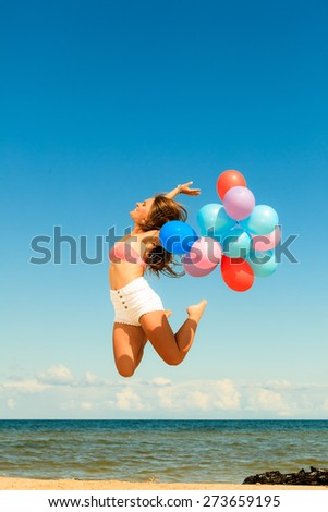 Summer holidays, celebration and lifestyle concept - attractive athletic woman teen girl jumping with colorful balloons outside on beach, sunny day - stock photo