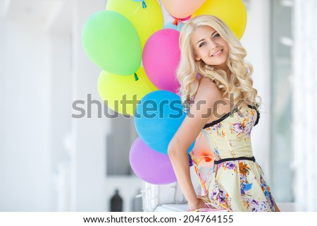 summer holidays, celebration and lifestyle concept - beautiful woman with colorful balloons in the city. Happy young woman with colorful latex balloons keeping her dress, urban scene, outdoors
