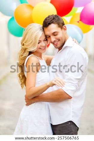 summer holidays, celebration and wedding concept - couple with colorful balloons and engagement ring - stock photo