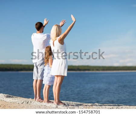 summer holidays, celebration, children and people concept - happy family at the seaside with greeting gesture