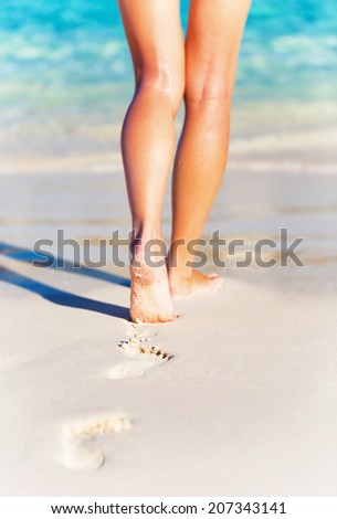 Summer holidays concept, closeup photo of a sexy woman's legs, slim female walking on the beach, carefree lifestyle, summer vacation background, relaxation and life joy - stock photo