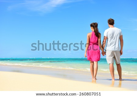 Summer holidays - couple on tropical beach vacation standing in white sand relaxing looking at ocean view. Romantic young adults holding hands in beachwear with pink dress and surf shorts in love. - stock photo