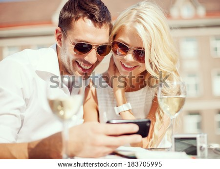 summer holidays, dating and technology concept - couple looking at smartphone in cafe in the city - stock photo