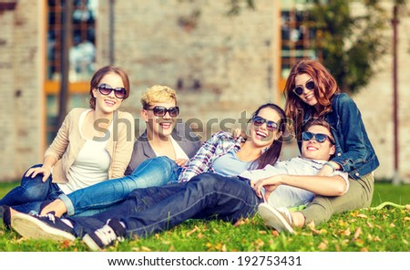summer holidays, education, campus and teenage concept - group of students or teenagers hanging out outdoors
