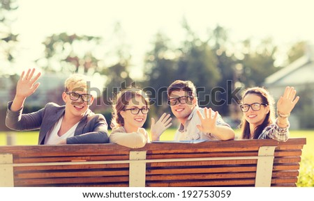 summer holidays, education, campus and teenage concept - group of students or teenagers in eyeglasses waving hands - stock photo
