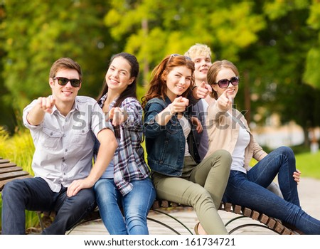 summer holidays, education, campus and teenage concept - group of students or teenagers pointing fingers of hands at you - stock photo
