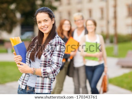 summer holidays, education, campus and teenage concept - smiling teenage girl with folders and classmates on the back - stock photo