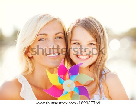 summer holidays, family, children and people concept - happy mother and child girl with pinwheel toy - stock photo