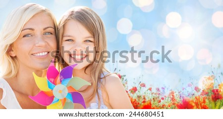 summer holidays, family, children and people concept - happy mother and girl with pinwheel toy over blue lights and poppy field background - stock photo