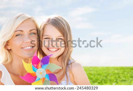 summer holidays, family, children and people concept - happy mother and girl with pinwheel toy over blue sky and grass background - stock photo
